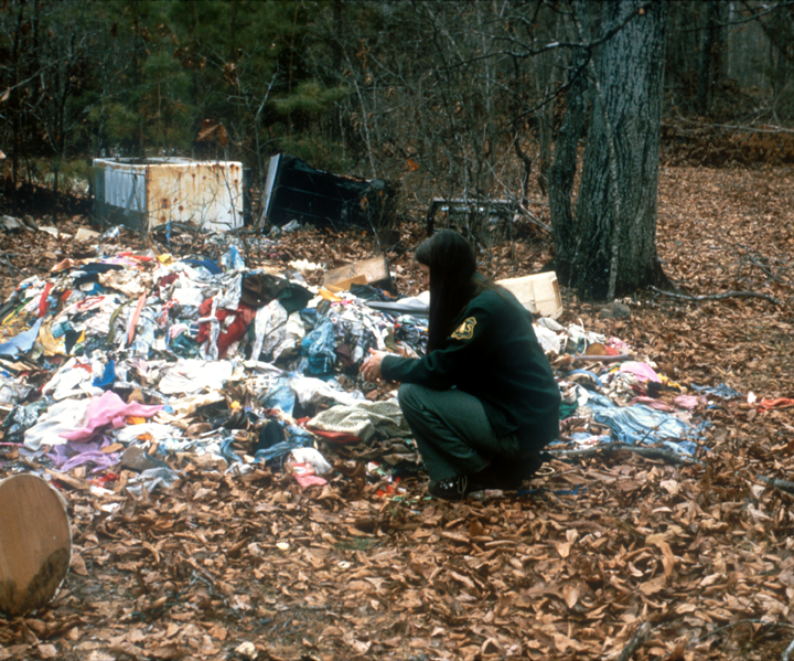 A female Forest Service employee crouches down near a massive pile of garbage.